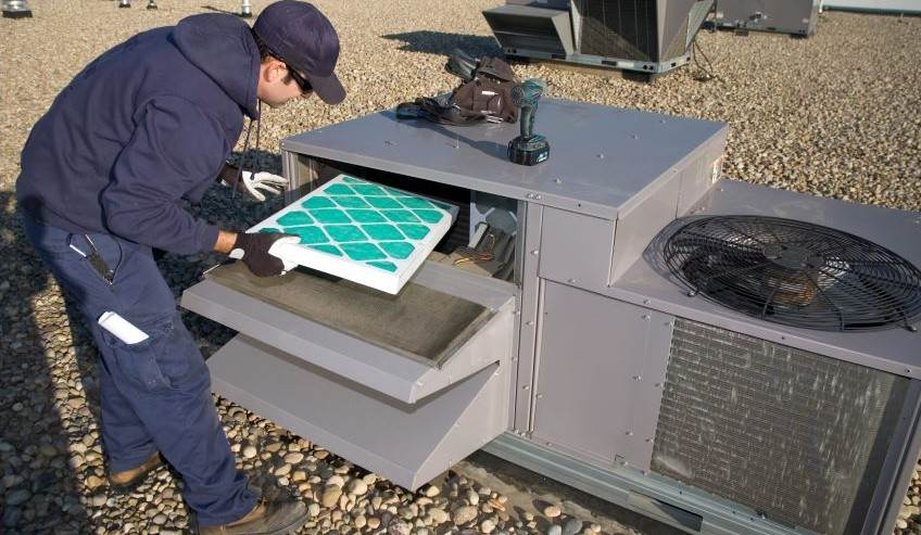 Man replacing an air filter in commercial air conditioner unit