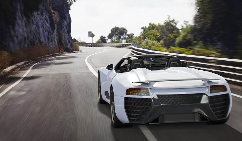 Sports car convertible driving down the road.