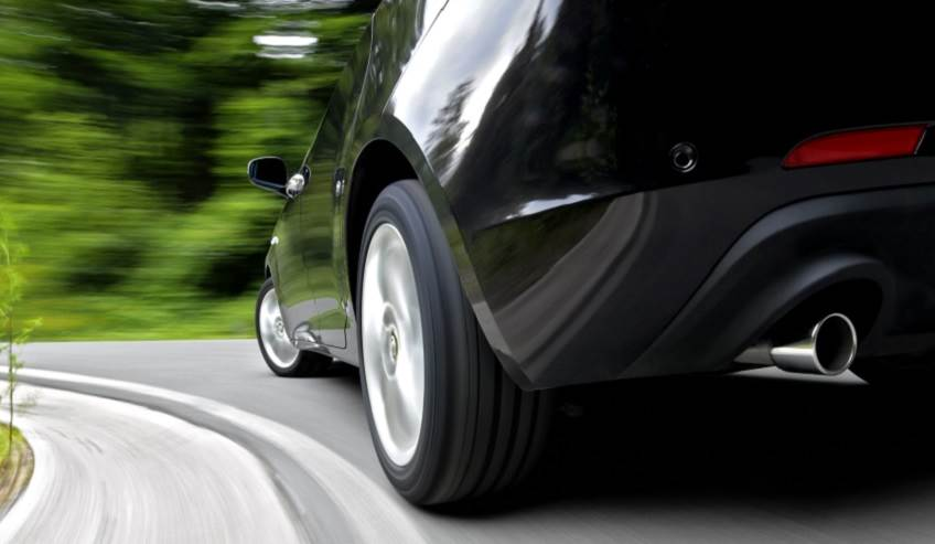 Closeup of a car driving down the road.